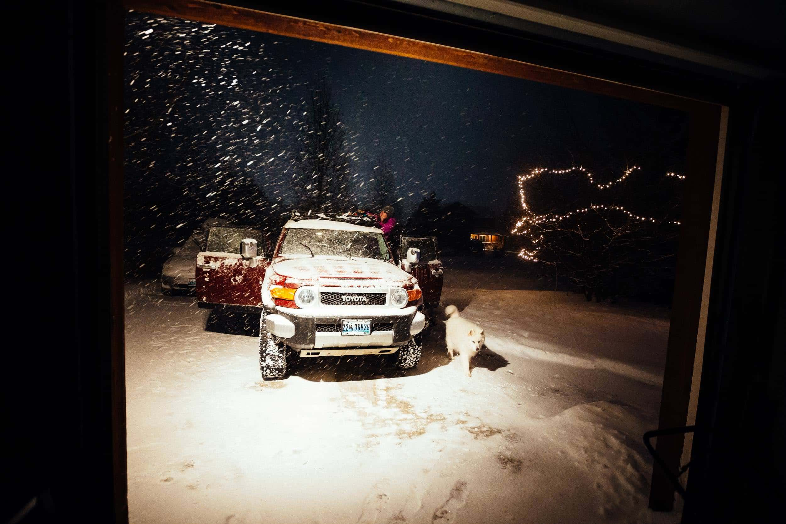 Heather Goodrich unloads skis off of the roof of the FJ Cruiser after a day of powder skiing at Christmas