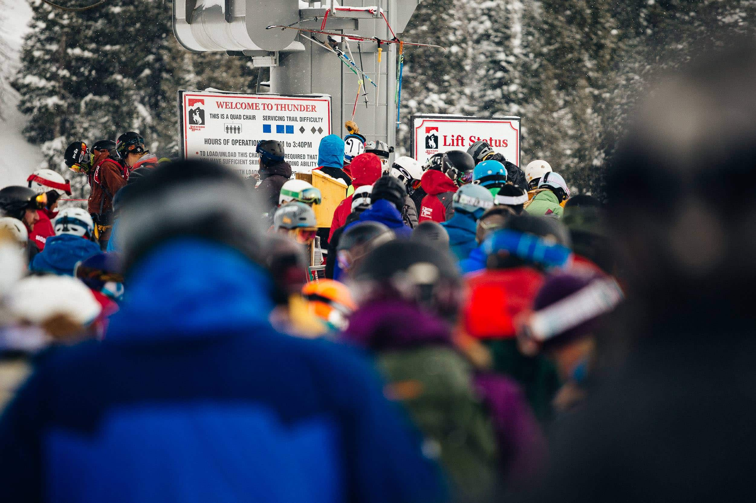 Skiers wait on line at the Thunder chair as a lone skier hits the pole chimes
