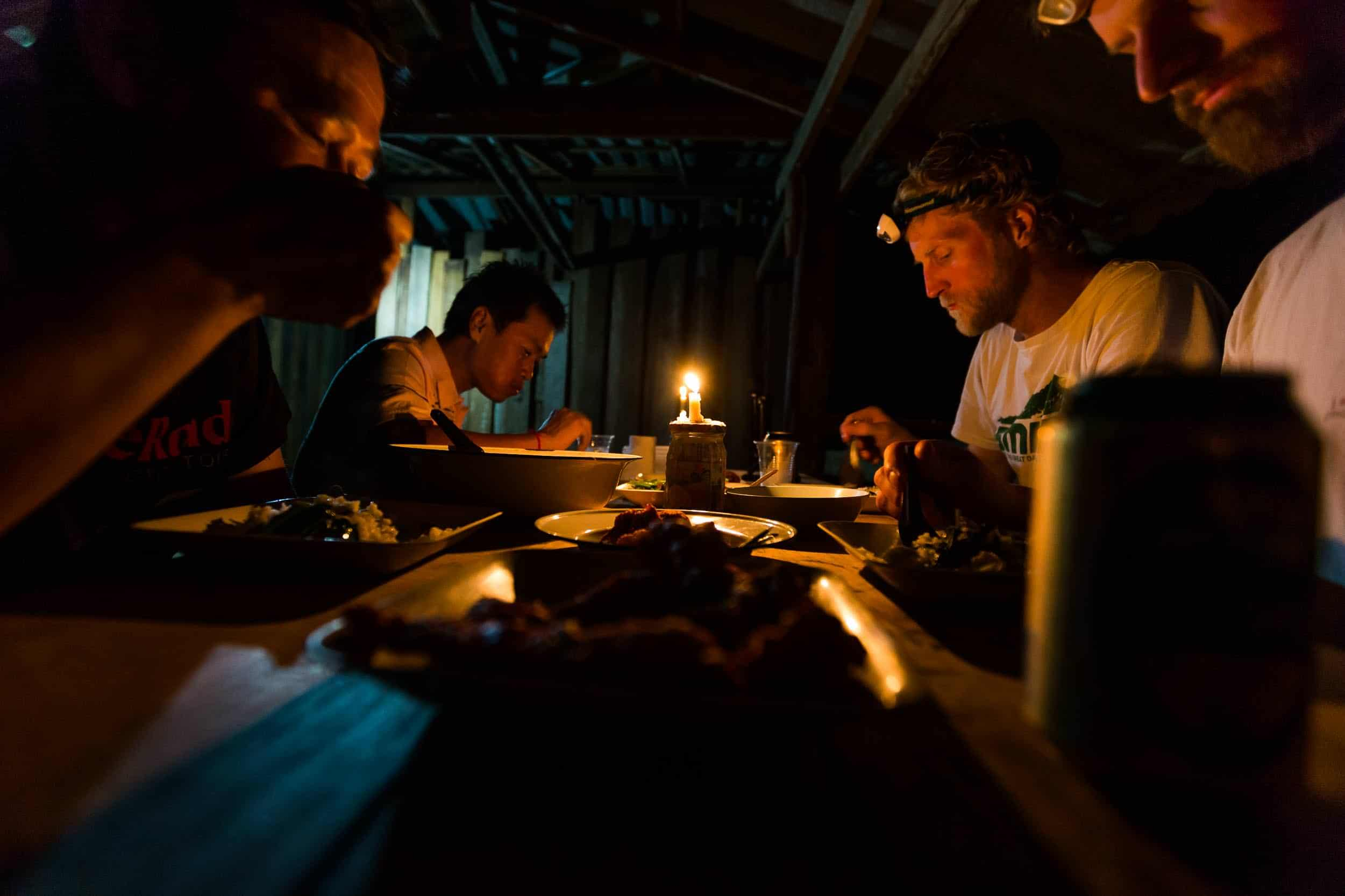 Andrew Whiteford, Jay Goodrich, Mr. Sak, and Win Jalawin eat dinner in local tribe member's house in the higher altitude jungle near Ban Sop Gai, Thailand