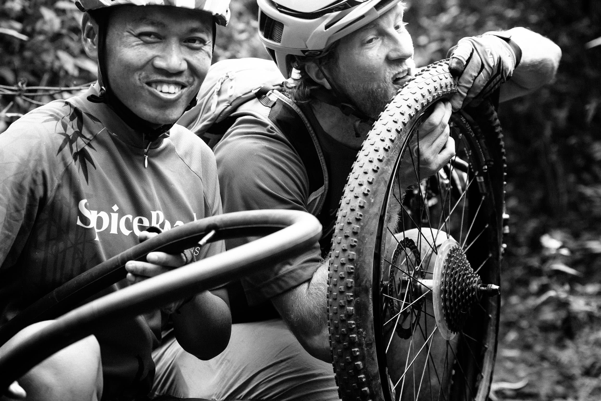 Andrew Whiteford and Win Jalawin fix a flat tire on the single track in the jungle near Ban Sop Gai, Thailand
