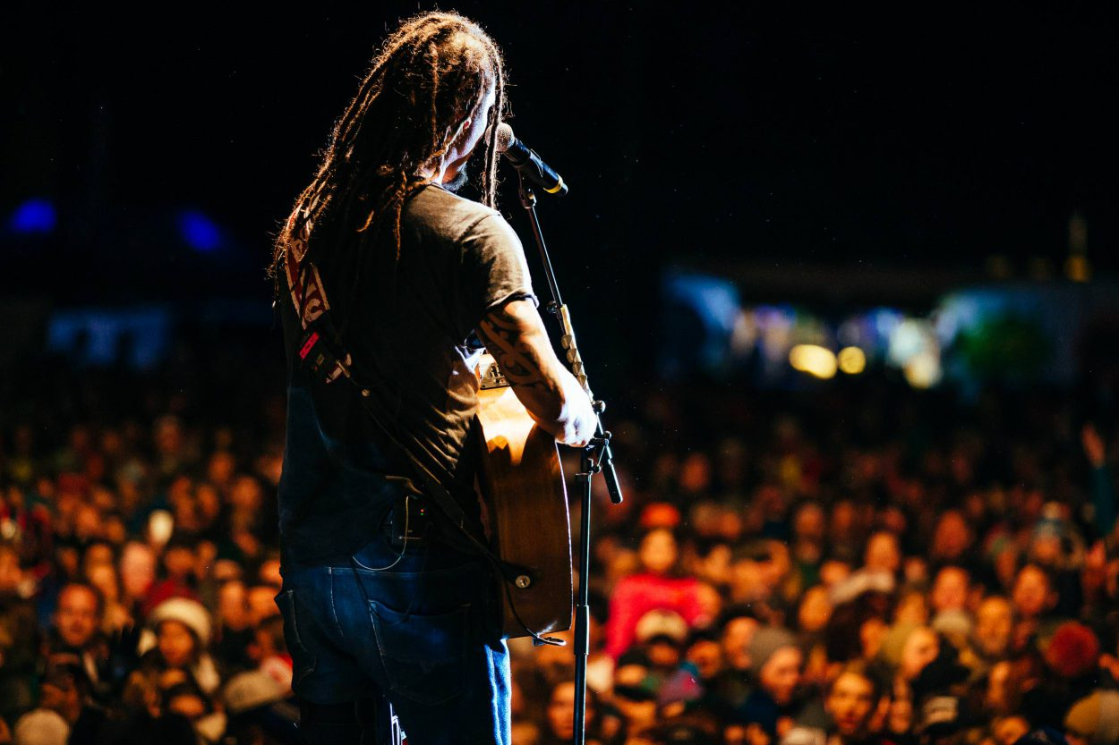 Portrait of Michael Franti on stage with guitar for Wyoming Tourism