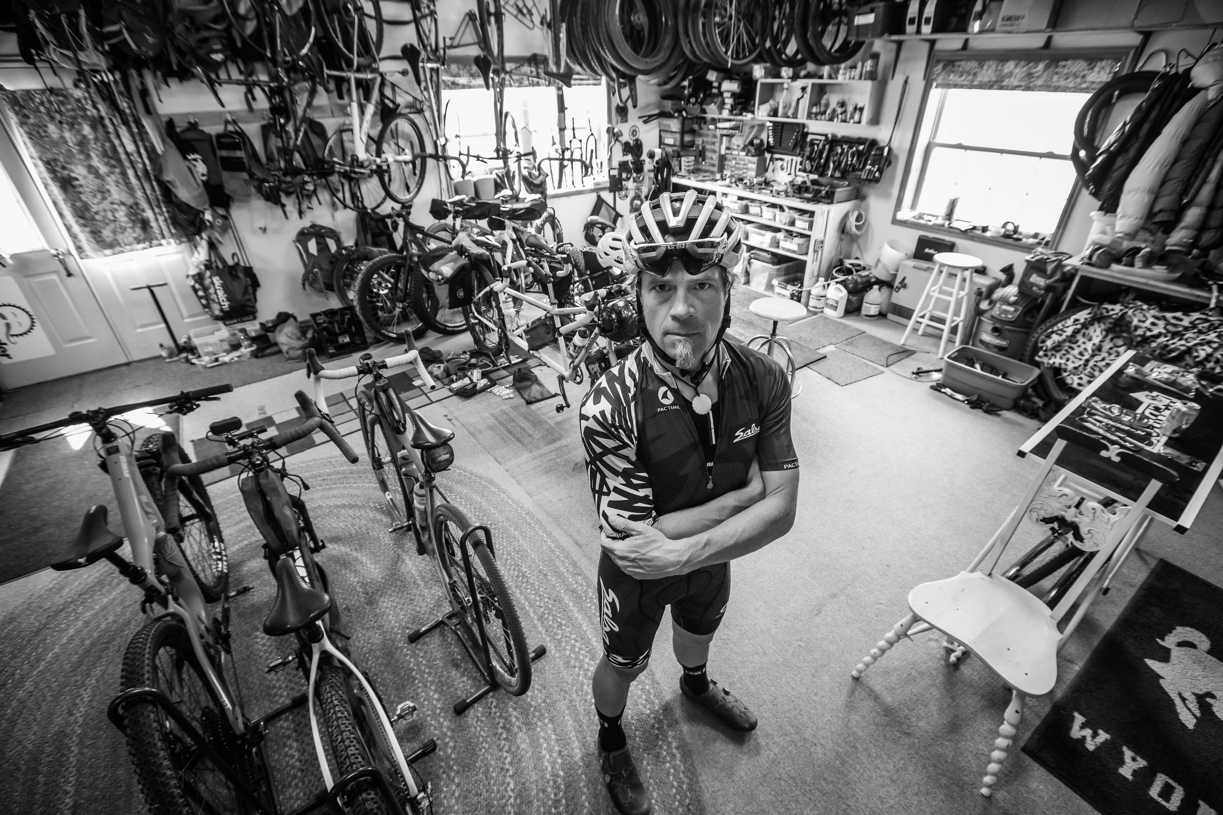 Jay Petervary poses for a portrait in his bicycle man cave - adventure photography commissions - by Jay Goodrich